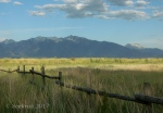West Jordan Preserve with mountains and clouds and fencerails