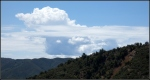 Close up anvil cloud and near forested high desertmountain