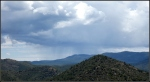 Distant rain and clouds over high desert forestedmountains