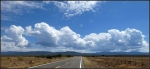 Summer clouds over highway 89 with mountains and fenceline